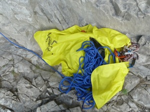 The large tarp has a hole in the middle. The rope slides through into the bag.