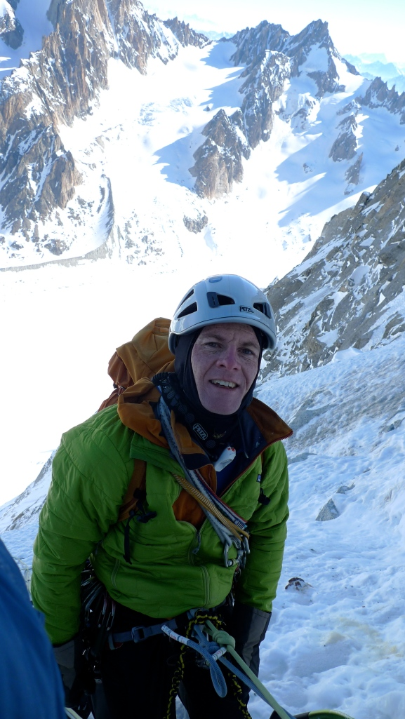 The author using a lightweight belay jacket during a brief stop on the North Face of Les Droites, Chamonix, France.
